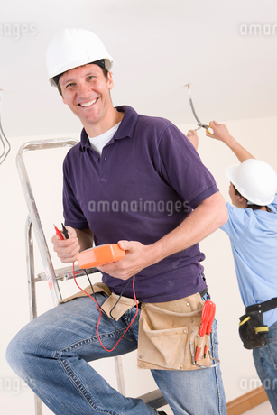 Smiling electrician holding voltmeter on ladder with co-worker wiring ceiling in backgroundの写真素材 [FYI02117553]