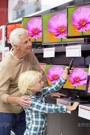 Grandfather and grandson with remote control looking at televisions in electronics storeの写真素材 [FYI02117560]