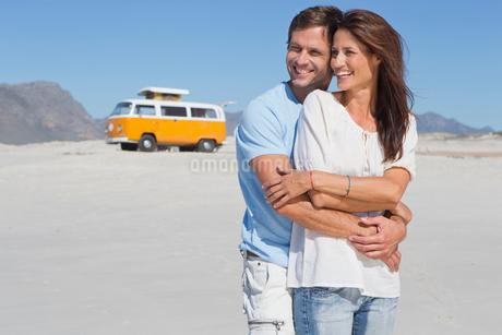 Happy couple hugging on sunny beach with van in backgroundの写真素材 [FYI02117567]