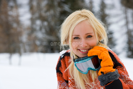 Young woman in snow field, holding ski goggles, smiling, portraitの写真素材 [FYI02117573]