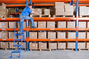 Worker standing on shelf and reaching for cardboard box in distribution warehouseの写真素材 [FYI02117586]