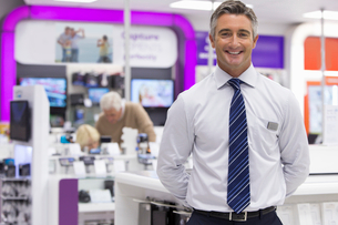 Portrait of smiling salesman in electronics storeの写真素材 [FYI02117587]