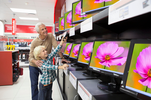 Grandfather and grandson holding remote control and looking up at televisions in electronics storeの写真素材 [FYI02117588]