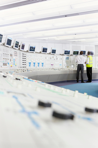 Engineers looking up at computer monitors in control room of nuclear power stationの写真素材 [FYI02117595]