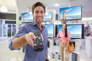 Portrait of smiling man holding remote control in front of televisions in electronics storeの写真素材 [FYI02117609]