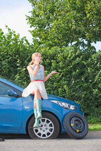 Woman With Flat Tyre On Car Phoning For Assistanceの写真素材 [FYI02117612]