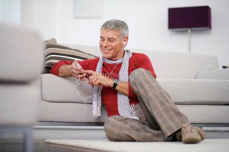 Happy senior man listening to iPod at homeの写真素材 [FYI02117620]