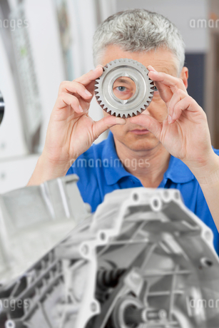 Portrait of engineer peering through gear wheel with engine block in foregroundの写真素材 [FYI02117629]