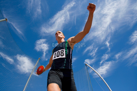 Male athlete preparing to throw discus, low angle viewの写真素材 [FYI02117642]