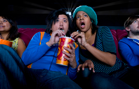 Couple in cinema sharing drink, making faces, low angle viewの写真素材 [FYI02117681]