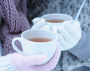 Close-up of two young women holding hot tea on winter dayの写真素材 [FYI02117695]
