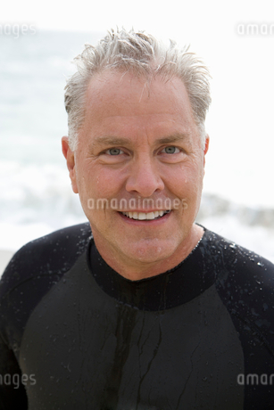Man in wetsuit, smiling, portrait, close-upの写真素材 [FYI02117697]