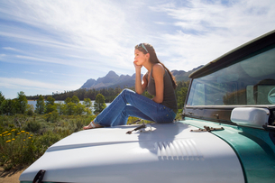Young woman sitting on bonnet of parked jeep in mountain valley, admiring scenery, profileの写真素材 [FYI02117705]
