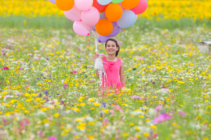 Portrait of smiling girl holding bunch of balloons among wildflowers in sunny meadowの写真素材 [FYI02117717]