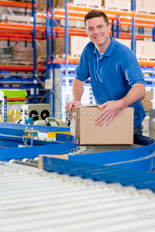 Portrait of smiling worker with cardboard box on production line in distribution warehouseの写真素材 [FYI02117738]