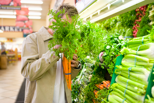 Man choosing carrots in grocery storeの写真素材 [FYI02117761]