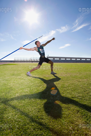 Male athlete preparing to throw javelin, low angle view (lens flare)の写真素材 [FYI02117766]