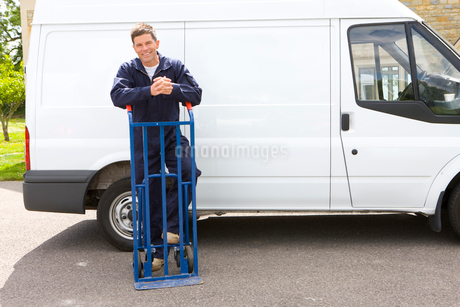 Smiling man in coveralls leaning on hand truck near work vanの写真素材 [FYI02117768]