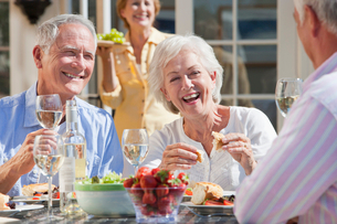 Smiling senior couples drinking wine and enjoying lunch on sunny patioの写真素材 [FYI02117771]