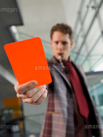Man in suit holding penalty red cardの写真素材 [FYI02117798]