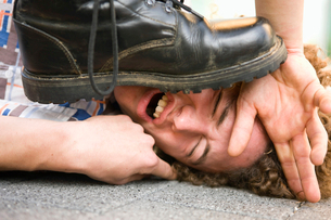 Young man lying on ground being stepped on by someone wearing black bootの写真素材 [FYI02117815]