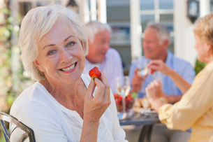 Portrait of smiling senior woman eating strawberry on patio with friends enjoying wine and lunch inの写真素材 [FYI02117837]