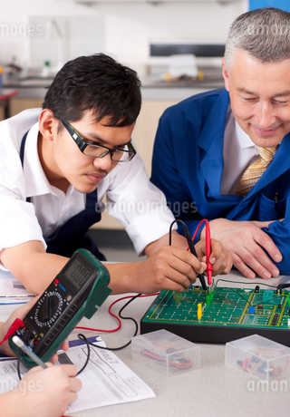 Teacher watching students working on electronic device in vocational classの写真素材 [FYI02117877]