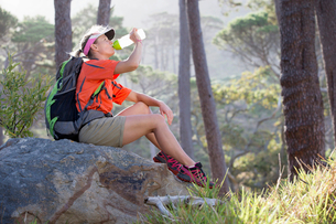 Woman with backpack drinking water in woodsの写真素材 [FYI02117893]