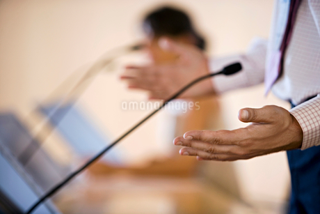 Businessman and businesswoman giving presentation, side view, focus on microphone in foregroundの写真素材 [FYI02117935]