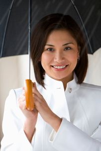 Businesswoman standing outside in pouring rain, holding umbrella, smiling, close-up, front view, porの写真素材 [FYI02117953]