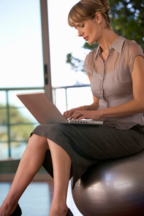 A businesswoman sitting in a gym using a laptopの写真素材 [FYI02117967]