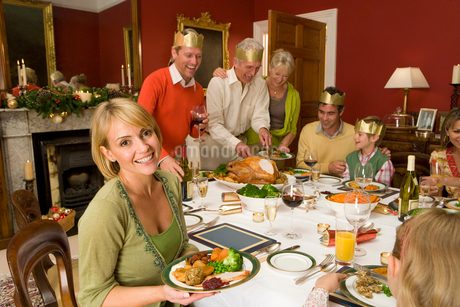 Family having Christmas dinner, portrait of woman smilingの写真素材 [FYI02117972]