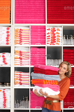 Woman shopping in department store, holding large pile of towels beside shelf, smiling, portraitの写真素材 [FYI02117978]