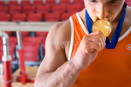 Male gymnast kissing gold medal around neck, close-upの写真素材 [FYI02118013]