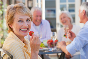 Portrait of smiling senior woman eating strawberry on patio with friends enjoying wine and lunch inの写真素材 [FYI02118017]
