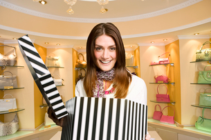 Excited woman opening hat box in expensive boutiqueの写真素材 [FYI02118026]