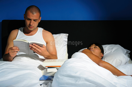 Young couple relaxing in bed, studio shotの写真素材 [FYI02118031]