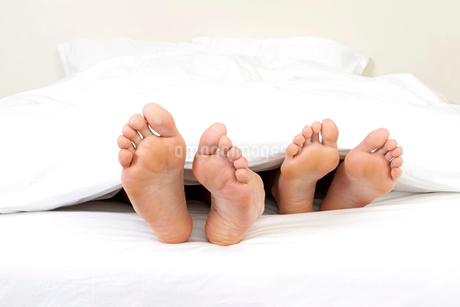 Close-up of feet of couple in bedの写真素材 [FYI02118077]