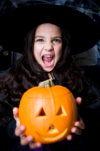 Girl in a witch's costume at a Hallowe'en party, holding a pumpkin with a carved faceの写真素材 [FYI02118084]