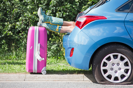 Woman With Flat Tyre On Car Resting Feet On Suitcaseの写真素材 [FYI02118143]