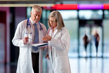 Doctors looking at paperwork together in hospital hallwayの写真素材 [FYI02118147]