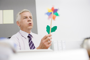 A mature businessman sitting at a desk blowing a toy windmillの写真素材 [FYI02118198]