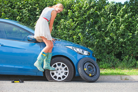 Frustrated Woman Broken Down With Flat Tyre On Carの写真素材 [FYI02118212]