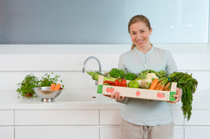 Woman in kitchen with box of vegetables, smiling, portraitの写真素材 [FYI02118224]
