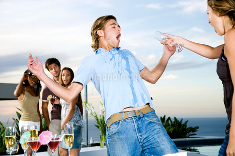 Woman throwing her drink over a man at a partyの写真素材 [FYI02118227]