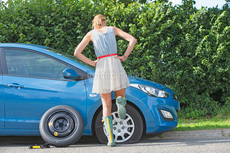 Frustrated Woman Broken Down With Flat Tyre On Carの写真素材 [FYI02118248]