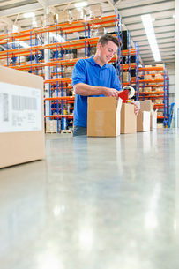 Worker taping cardboard boxes on production line in distribution warehouseの写真素材 [FYI02118269]