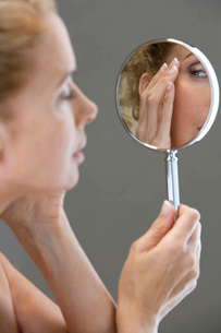 A middle-aged woman looking at her face in the mirrorの写真素材 [FYI02118274]