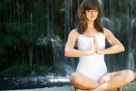 A woman meditating by a waterfallの写真素材 [FYI02118283]