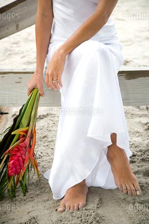 A bride sitting on a beachの写真素材 [FYI02118300]